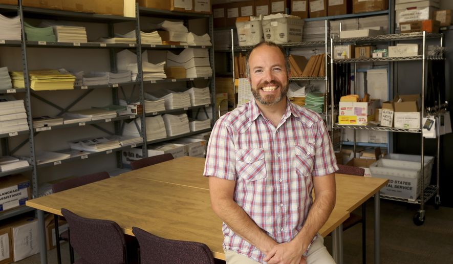 In this June 21, 2018 photo, Jeremy Johnson, State of Alaska Division of Elections Region III Elections Supervisor, poses in the supply room in the Division of Elections office in downtown Fairbanks, Alaska. Johnson went to college to get a degree in biology, but a perfectly timed internship in the Capitol in Juneau diverted him toward local and state politics. (Eric Engman/Fairbanks Daily News-Miner via AP)