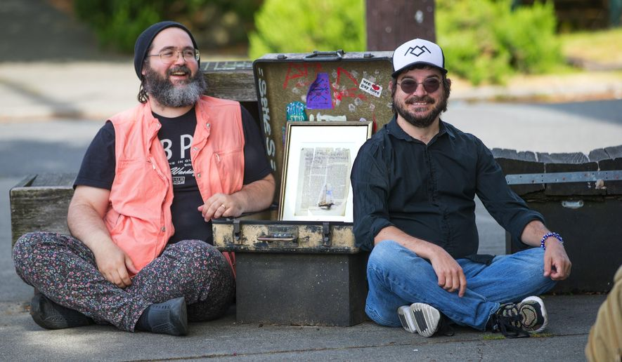 In this June 12, 2018 photo, Seattle residents Garrett Kelly, left and Jeremy Puma, sitting next to the Time Travel Mailbox located at 20th and Union, are creating a crowd sourced map of Liminal Seattle that shows people all the magical and liminal places in town. Kelly found a message in the mailbox thanking the recipient for believing in time travel. (Mike Siegel/The Seattle Times via AP)