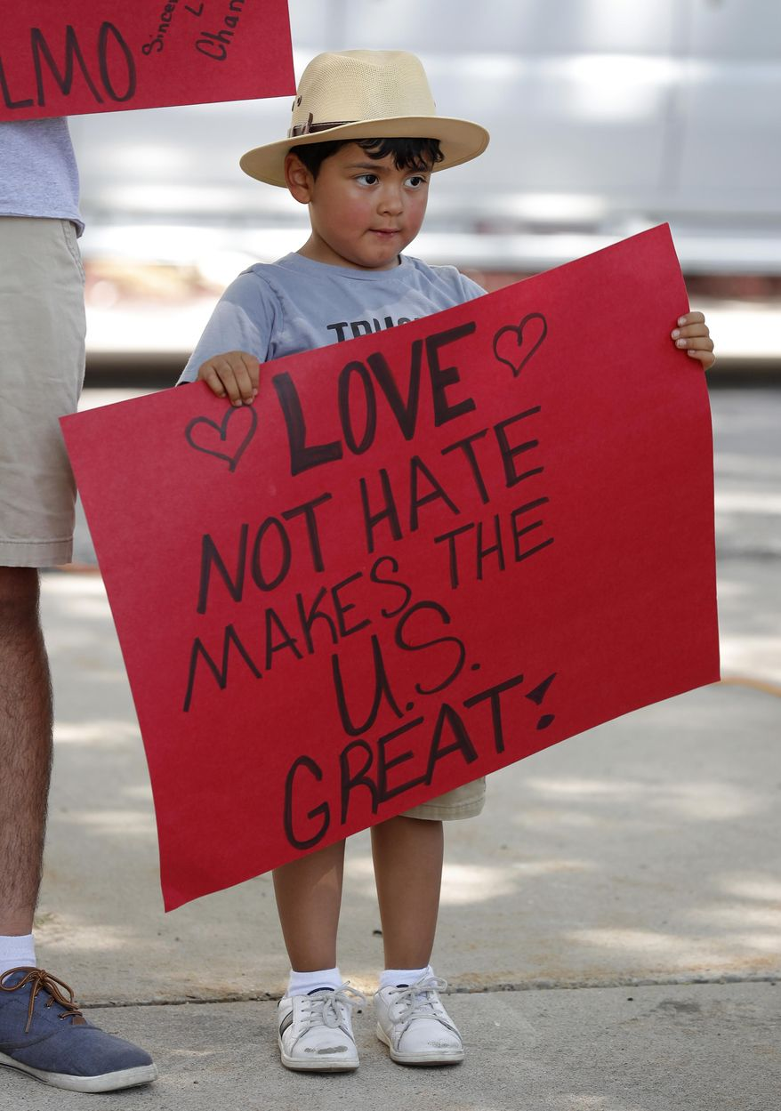 Four-year-old Carlos Gonzalez, of Marshalltown, Iowa, holds a sign during a rally to protest the Trump administration's immigration policies, Saturday, June 30, 2018, outside the Marshall County Courthouse in Marshalltown, Iowa. (AP Photo/Charlie Neibergall)