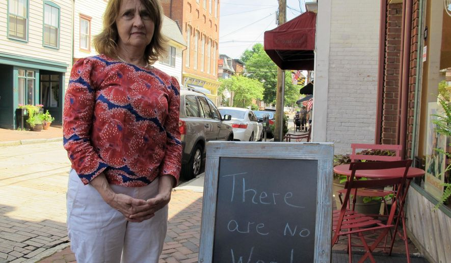 Mary Adams, owner of The Annapolis Bookstore, stands by a sign outside her store on Saturday, June 30, 2018 in downtown Annapolis, Md. Adams, who knew two of the journalists who were killed in the attack on The Capital newspaper, said the shooting has made the entire community very sad. (AP Photo/Brian Witte)