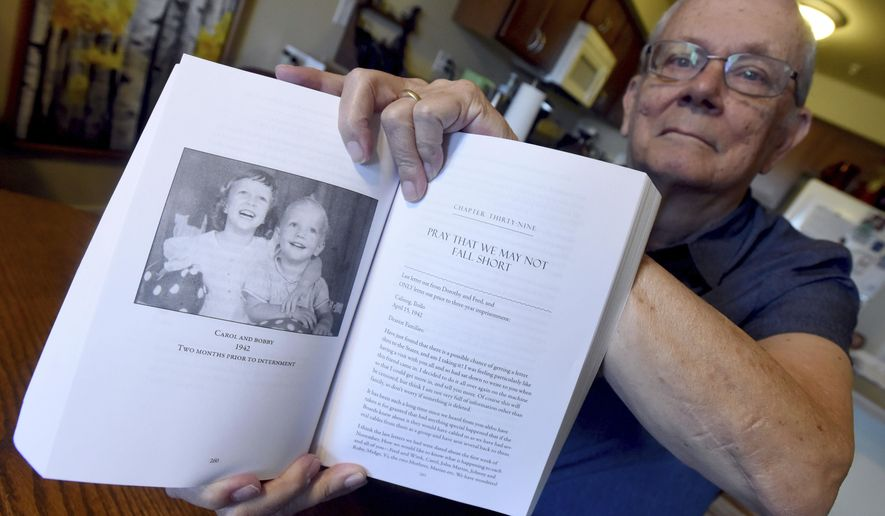 "In this June 21, 2018 photo, Robert Chambers shows a photo of his sister and himself featured in the book ""Courage in a White Coat,"" while at his home in Loveland, Colo.(Joshua Polson/The Greeley Tribune via AP)"