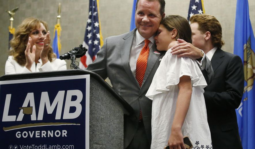 FILE - In this Tuesday, June 26, 2018 file photo, Oklahoma Lt. Gov. Todd Lamb hugs his daughter Lauren as he gives a concession speech in the Republican primary for Governor in Oklahoma City. At left is his wife Monica, and at right is his son Griffin. Oklahoma voters are gearing up for the next round of statewide elections after turning out in large numbers for primary election balloting. Six incumbent Republican lawmakers lost their jobs and others were cast into runoffs on Aug. 28. Lamb, an early favorite to replace term-limited GOP Gov. Mary Fallin, was defeated. (AP Photo/Sue Ogrocki, File)