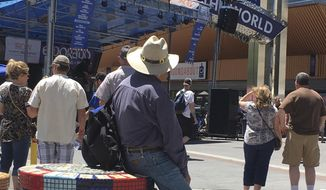 Visitors to the BBQ, Brews and Blues festival listen to a band in downtown Reno on June 16, 2018. The number of tourists visiting Reno-Sparks and Washoe County over the past year topped the 5 million mark for the first time since 2007. (AP Photo/Scott Sonner).