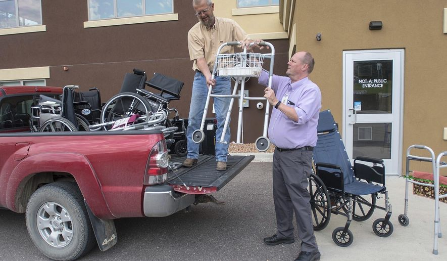 Gregg Olson, left, takes a walker from Mike Lagerquist of VINE Faith in Action outside the senior center's building Friday, June 15, 2018 in Mankato. Olson collects old walkers and wheelchairs until he has enough to fit a trailer, at which point he takes the haul to the Twin Cities where they are refurbished and sent to countries around the world for those in need of them. (Jackson Forderer/The Free Press via AP)
