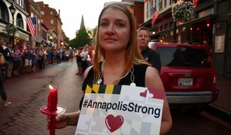 A woman is shown here participating in the June 29, 2018 Annapolis vigil remembering the five dead in the previous day's shooting rampage at The Capital newspaper. (Julia Airey/The Washington Times)