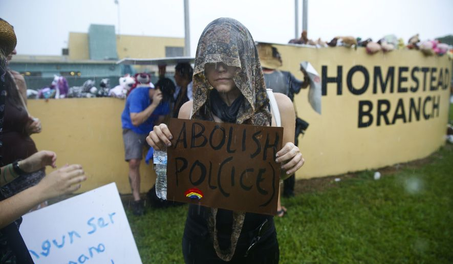 A protesters holds up a sign the says 'abolish pol(ice)' after she marches to the Homestead Temporary Shelter for Unaccompanied Children, on Saturday, June 23, 2018, in Homestead, Fla. (AP Photo/Brynn Anderson)