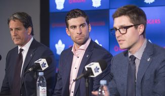 John Tavares, center, sits alongside Toronto Maple Leafs general manager Kyle Dubas, right, and president Brendan Shanahan following a news conference after Tavares signed with the Maple Leafs NHL hockey team Sunday, July 1, 2018, in Toronto. (Chris Young/The Canadian Press via AP) **FILE**
