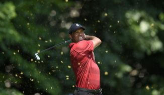 Tiger Woods watches his tee shot on the fifth tee during the final round of the Quicken Loans National golf tournament, Sunday, July 1, 2018, in Potomac, Md. (AP Photo/Nick Wass)
