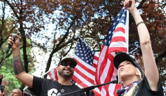 U.S. Senate candidate for Washington, Joey Gibson, left, who is the leader of Vancouver-based Patriot Prayer, leads a rally in downtown Portland, Ore., Saturday, June 30, 2018. (Mark Graves/The Oregonian via AP)