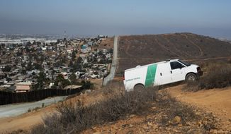 A U.S. Border Patrol van drives up the hill to pick up migrants apprehended trying to cross the U.S.-Mexico border illegally as the Mexican land looks on the left side of the border wall along a road Thursday, June 28, 2018, in San Diego. (AP Photo/Jae C. Hong, File)