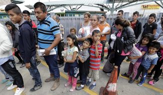 Immigrant families lined up to enter the central bus station after they were processed and released by U.S. Customs and Border Protection last month in McAllen, Texas. (Associated Press/File)