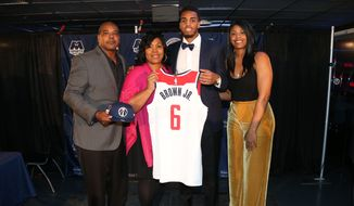 Troy Brown Jr. (center, in suit), the Washington Wizards' first-round draft pick in 2018, poses at Capital One Arena in Washington, D.C. with father Troy Brown Sr. (left), mother Lynn Brown and one of his sisters. (Photo courtesy of Twitter / @WashWizards)