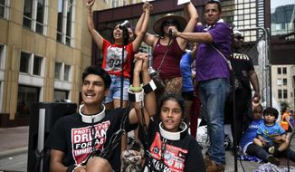 James Gutierrez, 15, and his sister, Lilah, 8, wore chains during a demonstration against the Trump administration's immigration policies Saturday, June 30, 2018.(Aaron Lavinsky/Star Tribune via AP)