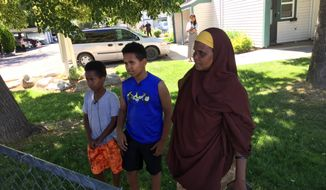 Fathi Mahamoud, 11, left, Esrom Habte, 12, center, and Thado Aip describe the Saturday night attack that left nine fellow residents of their Boise, Idaho, apartment complex with stabbing injuries, Sunday, July 1, 2018. Police have arrested a suspect in the case. (AP Photo/Rebecca Boone)