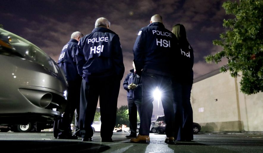 In this Jan. 10, 2018, file photo, U.S. Immigration and Customs Enforcement agents gather before serving a employment audit notice at a 7-Eleven convenience store in Los Angeles. (AP Photo/Chris Carlson, File)