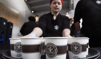 A barista prepares to serve sample-sized coffee cups before the annual Starbucks shareholders meeting in Seattle on March 21, 2012. (Associated Press) ** FILE **