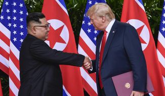 In this June 12, 2018, file photo, North Korea leader Kim Jong-un, left, and U.S. President Donald Trump shake hands at the conclusion of their meetings at the Capella resort on Sentosa Island in Singapore. (AP Photo/Susan Walsh, Pool, File)