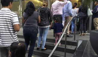 In this June 28, 2018, photo, people line up outside the building that houses the immigration courts in Los Angeles. In recent weeks, immigration judges have been thrust into the center of the heated political controversy over how the Trump administration is handling the cases of mostly Central American immigrants caught on southwest border. (AP Photo/Amy Taxin)