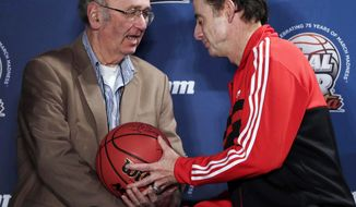 FILE - In this April 7, 2013, file photo, Associated Press college basketball writer Jim O'Connell, left, is honored by Louisville coach Rick Pitino after a news conference at the NCAA Final Four college basketball tournament in Atlanta. O'Connell died Monday, July 2, 2018. He was 64. (AP Photo/Chris O'Meara, File)