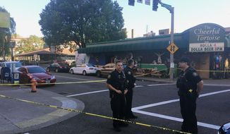 FILE - In this June 29, 2018, file photo, police officers stand at the scene of an earlier shooting outside The Cheerful Tortoise bar in Portland, Ore. A black man who was fatally shot by Portland State University campus police during a fight outside the bar had a permit to carry a concealed handgun. (Shane Dixon/The Oregonian via AP, File)