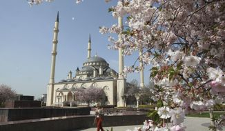In this April 6, 2016, file photo, a woman walks outside the main mosque in the downtown Chechen regional capital of Grozny, Russia. (AP Photo/Musa Sadulayev, File)