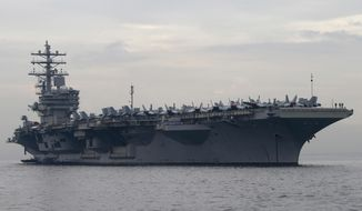 In this June 26, 2018, file photo, the U.S. aircraft carrier USS Ronald Reagan anchors off Manila Bay for a goodwill visit in Manila, Philippines. The U.S. military has deployed the third aircraft carrier this year to patrol the South China Sea, where Washington has criticized China's military buildup on new man-made islands. (AP Photo/Bullit Marquez, File)
