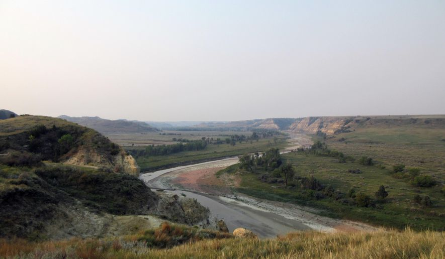 """This Sept. 3, 2017 photo shows a curving river at Theodore Roosevelt National Park in Medora, N.D., marking the landscape in colorful patterns as it interacts with soil and stone. Teddy Roosevelt spent time in the area to grieve after his wife and mother died the same day, and his experiences there turned the future president into one of America's greatest conservationists. He described the area as """"a land of vast silent spaces _ a place of grim beauty."""" (AP Photo/Beth J. Harpaz)"""