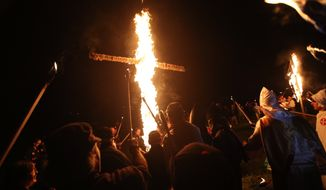 "In this Saturday, April 23, 2016 photo, members of the Ku Klux Klan participate in cross burnings after a ""white pride"" rally in rural Paulding County near Cedar Town, Ga. In 2016, KKK leaders say they feel that U.S. politics are going their way, as a nationalist, us-against-them mentality deepens across the nation. (AP Photo/John Bazemore)"