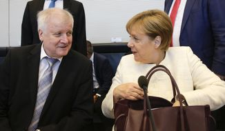 German Chancellor Angela Merkel, right, and Interior Minister Horst Seehofer, left, attend a special faction meeting of the Christian Union parties ahead, of a debate at the German parliament Bundestag at the Reichstag building in Berlin, Tuesday, July 3, 2018. (AP Photo/Markus Schreiber)