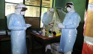 In this photo taken on Sunday, May 13, 2018, health care workers wear virus protective gear at a treatment center in Bikoro Democratic Republic of Congo. Congo's latest Ebola outbreak has spread to a city of more than 1 million people, a worrying shift as the deadly virus risks traveling more easily in densely populated areas. Two suspected cases of hemorrhagic fever were reported in the Wangata health zones that include Mbandaka, the capital of northwestern Equateur province. The city is about 150 kilometers (93 miles) from Bikoro, the rural area where the outbreak was announced last week, said Congo's Health Minister Oly Ilunga. (AP Photo/John Bompengo)
