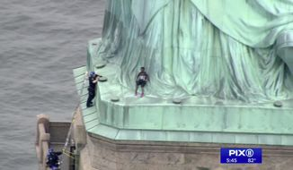 In this image made from video by PIX11, a person, center, leans against the robes of the Statue of Liberty on Liberty Island, as one of the police officers climbed up on a ladder to stand on a ledge nearby talking the climber into descending in New York, Wednesday, July 4, 2018. (PIX11 via AP)