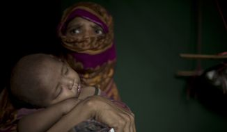 "In this Monday, June 25, 2018, photo, ""S"" holds her baby boy as she sits in her shelter in Kutupalong refugee camp in Bangladesh. ""S,"" a widow, was so worried about her neighbors discovering her pregnancy that she suffered silently through labor in her shelter, stuffing a scarf in her mouth to swallow her screams. (AP Photo/Wong Maye-E)"