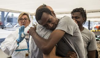 Migrants say goodbye to an aid worker as they disembark from the Open Arms aid boat, of Proactiva Open Arms Spanish NGO, after arriving at the port of Barcelona, Spain, Wednesday, July 4, 2018. The aid boat sailed to Spain with 60 migrants rescued on Saturday in waters near Libya, after it was rejected by both Italy and Malta. (AP Photo/Olmo Calvo)