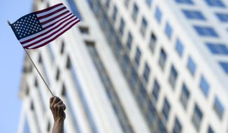 A woman waves an American flag during the 2018 AJC Peachtree Road Race in Atlanta, Wednesday, July 4, 2018. (Alyssa Pointer/Atlanta Journal-Constitution via AP)