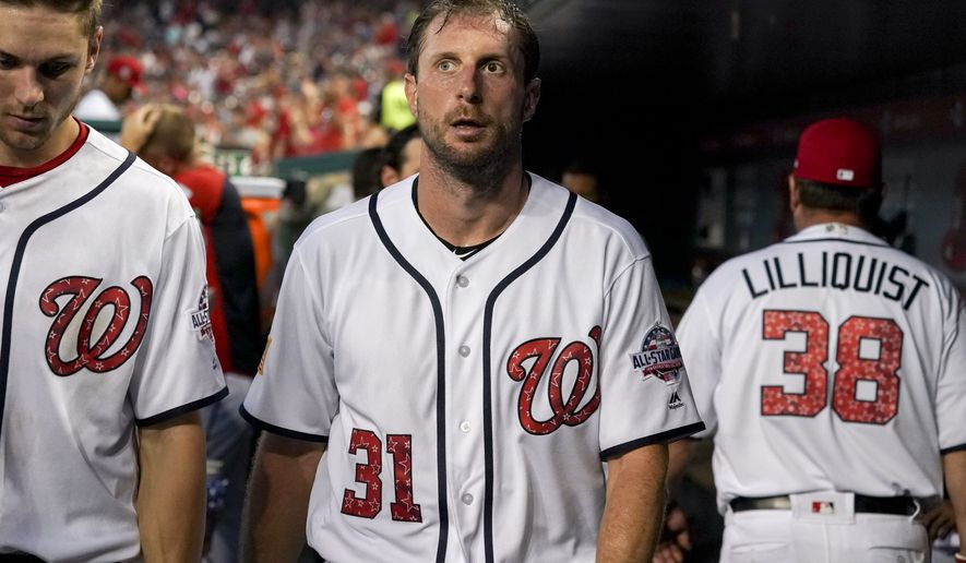 Washington Nationals starting pitcher Max Scherzer, center, walks through the dugout during a baseball game against the Boston Red Sox at Nationals Park, Monday, July 2, 2018, in Washington. (AP Photo/Andrew Harnik)