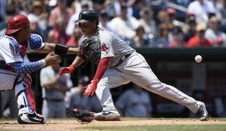 Boston Red Sox' Rafael Devers, right, slides home to score past Washington Nationals catcher Pedro Severino on a sacrifice fly by Jackie Bradley Jr., during the seventh inning of a baseball game Wednesday, July 4, 2018, in Washington. (AP Photo/Nick Wass)
