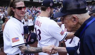 Milwaukee Brewers' Josh Hader shakes hands with a veteran at a ceremony before a baseball game against the Minnesota Twins Wednesday, July 4, 2018, in Milwaukee. (AP Photo/Morry Gash)