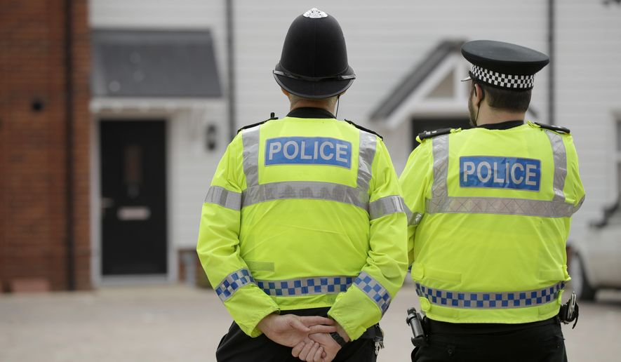 """British police officers stand facing a residential property in Amesbury, England, Wednesday, July 4, 2018. British police have declared a """"major incident"""" after two people were exposed to an unknown substance in the town, and are cordoning off places the people are known to have visited before falling ill.  (AP Photo/Matt Dunham)"""