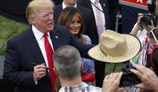 President Donald Trump, accompanied by first lady Melania Trump, hands back a signed hat as they greet military families during an afternoon picnic on the South Lawn of the White House, Wednesday, July 4, 2018, in Washington. (AP Photo/Alex Brandon)