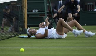 Spain's Garbine Muguruza falls trying to return the ball to Alison Van Uytvanck of Belgium, during their women's singles match, on the fourth day at the Wimbledon Tennis Championships in London, Thursday July 5, 2018. (AP Photo/Ben Curtis)