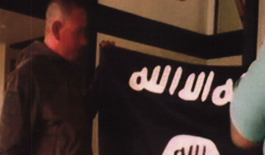 In this July 8, 2017, file image taken from FBI video and provided by the U.S. Attorney's Office in Hawaii on July 13, 2017, Army Sgt. 1st Class Ikaika Kang holds an Islamic State group flag after allegedly pledging allegiance to the terror group at a house in Honolulu. Newly unsealed court documents from an investigation into the Hawaii-based Army soldier accused of attempting to support the Islamic State group, provides more details about his obsession with the group's violence. (FBI/U.S Attorney's Office, District of Hawaii via AP, File)