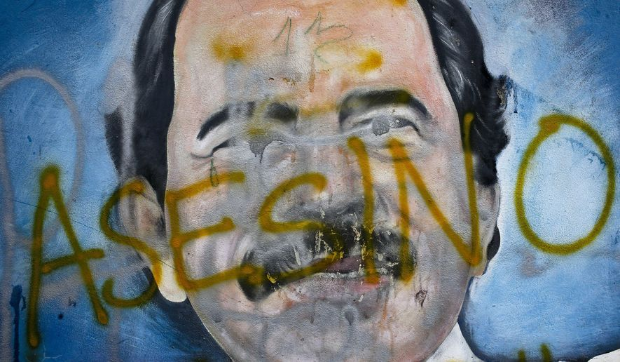 "In this May 26, 2018, photo, the Spanish word for ""Murderer"" covers a mural of Nicaragua's President Daniel Ortega, as part of anti-government protests demanding his resignation in Managua, Nicaragua. As of June 6, the non-governmental Nicaraguan Human Rights Center says the death toll since the start of the unrest in April is 129. (AP Photo/Esteban Felix)"