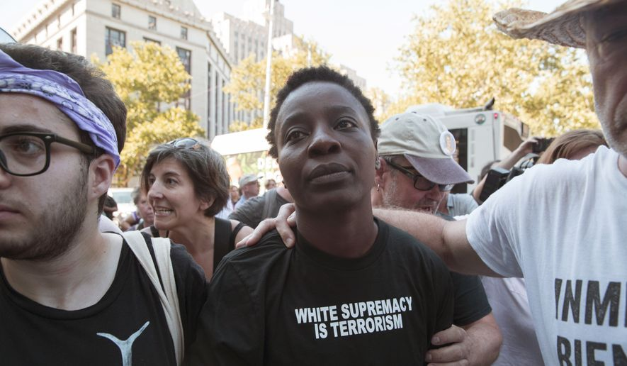 "Therese Okoumou is surrounded by supporters as she leaves federal court, Thursday, July 5, 2018, in New York. Okoumou, who climbed the base of the Statue of Liberty on a busy Fourth of July in what prosecutors called a ""dangerous stunt"" pleaded not guilty Thursday to misdemeanor trespassing and disorderly conduct. A federal judge released  Okoumou without bail after her court appearance. (AP Photo/Mary Altaffer)"