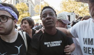 """Therese Okoumou is surrounded by supporters as she leaves Federal court, Thursday, July 5, 2018, in New York. Okoumou, who climbed the base of the Statue of Liberty on a busy Fourth of July in what prosecutors called a """"dangerous stunt"""" pleaded not guilty Thursday to misdemeanor trespassing and disorderly conduct . A federal judge released  Okoumou without bail after her court appearance.  (AP Photo/Mary Altaffer)"""