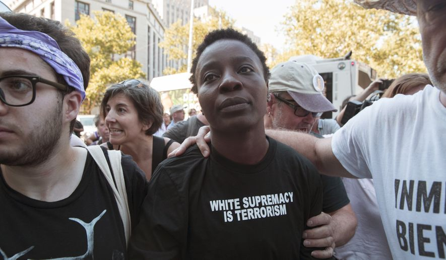 "Therese Okoumou is surrounded by supporters as she leaves Federal court, Thursday, July 5, 2018, in New York. Okoumou, who climbed the base of the Statue of Liberty on a busy Fourth of July in what prosecutors called a ""dangerous stunt"" pleaded not guilty Thursday to misdemeanor trespassing and disorderly conduct . A federal judge released  Okoumou without bail after her court appearance.  (AP Photo/Mary Altaffer)"