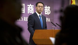 "In this March 29, 2018, photo, Chinese Ministry of Commerce spokesman Gao Feng listens to a reporter's question during a press conference at the Ministry of Commerce in Beijing. A Chinese government spokesman has said Thursday, July 5, 2018, that Beijing ""will not bow in the face of threats and blackmail"" on the eve of U.S. tariff hikes and will defend its interests. (AP Photo/Mark Schiefelbein)"