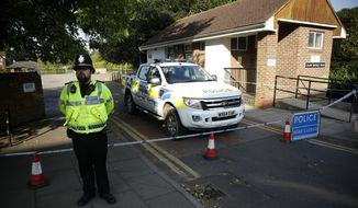 A British police officer guards a cordon which was extended overnight to include the Lush House car park adjacent to the Queen Elizabeth Gardens park in Salisbury, England, Thursday, July 5, 2018. British officials ware seeking clues Thursday in the rush to understand how two Britons were exposed to the military-grade nerve agent Novichok. (AP Photo/Matt Dunham)