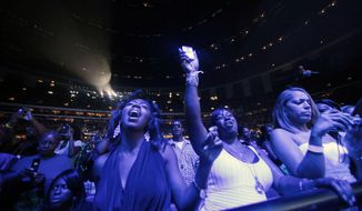 FILE- In this July 2, 2011 file photo, fans sing along with Jill Scott as she performs on stage at the 2011 Essence Music Festival in New Orleans.   More is the key word for the 2018 Essence Festival as it gears up for fans planning to descend upon New Orleans over the 4th of July holiday weekend for its 24th cultural explosion.  (AP Photo/Gerald Herbert, File)