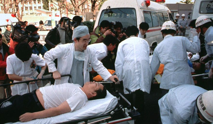 FILE - In this March 20, 1995, file photo, subway passengers affected by sarin nerve gas in the central Tokyo subway trains are carried into St. Luke's International Hospital in Tokyo. Japanese media reports say on Friday, July 6, 2018, doomsday cult leader Shoko Asahara, who has been on death row for masterminding the 1995 deadly Tokyo subway gassing and other crimes, has been executed. He was 63. (AP Photo/Chiaki Tsukumo, File)