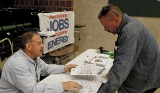 In this Thursday, Nov. 2, 2017, photo, a recruiter in the shale gas industry, left, speaks with an attendee of a job fair in Cheswick, Pa. (AP Photo/Keith Srakocic, File)
